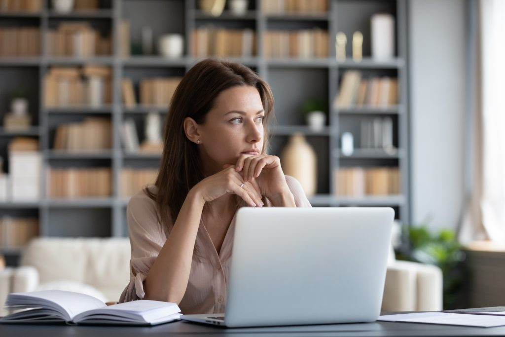 Woman sitting at desk with laptop looking pensive